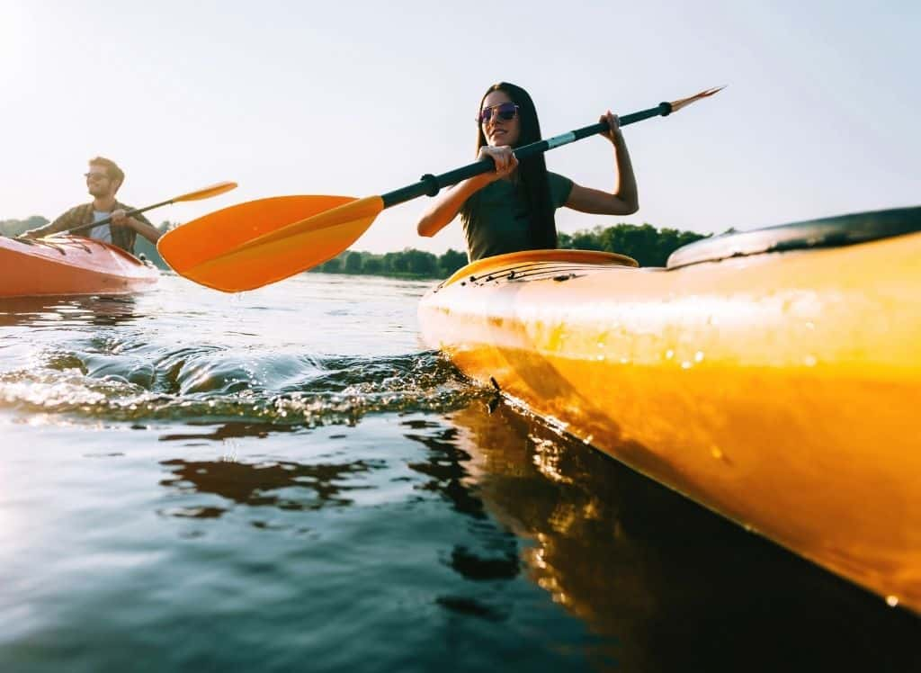 A man and woman going kayaking through the water.