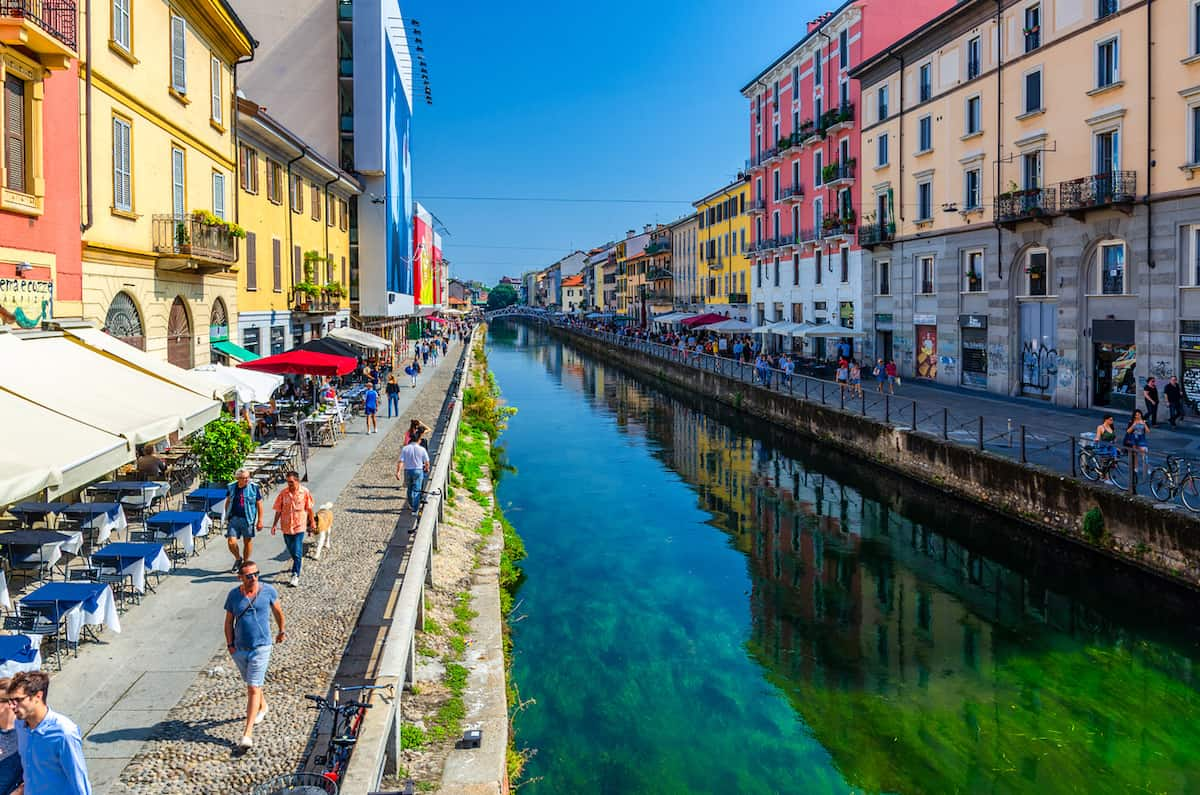 Colorful store fronts and people walking along the Navigili Canals in Milan on a warm day.