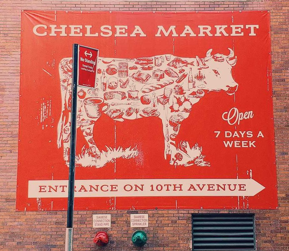 A red with a cow advertising for Chelsea Market.