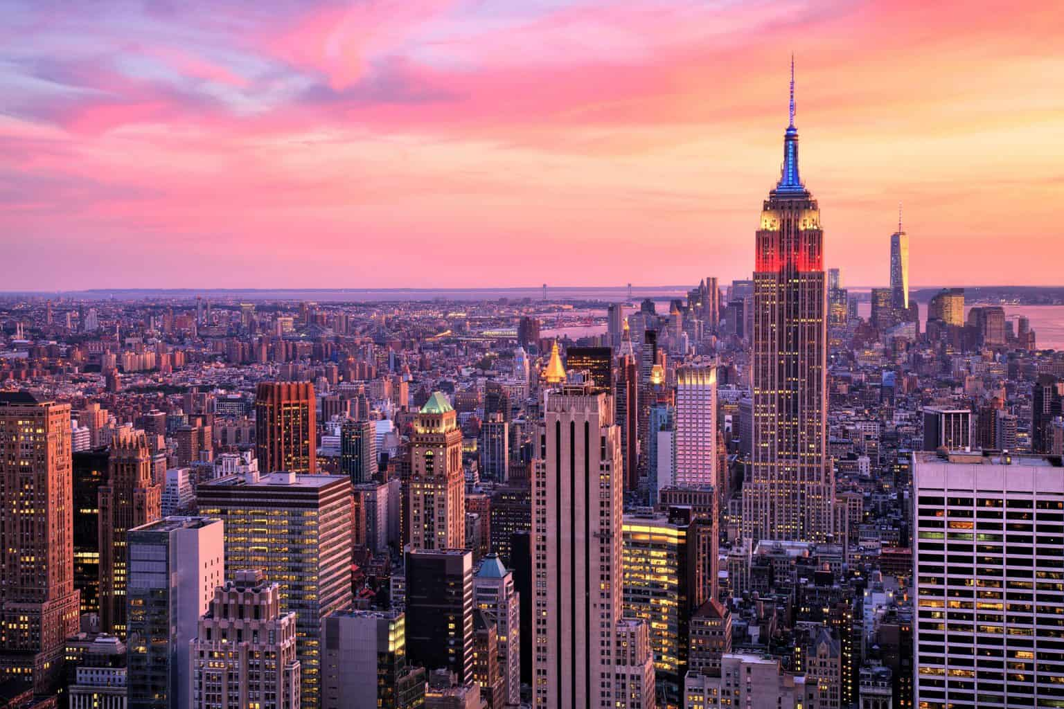 An aerial view of the empire state building lit up at sunset.