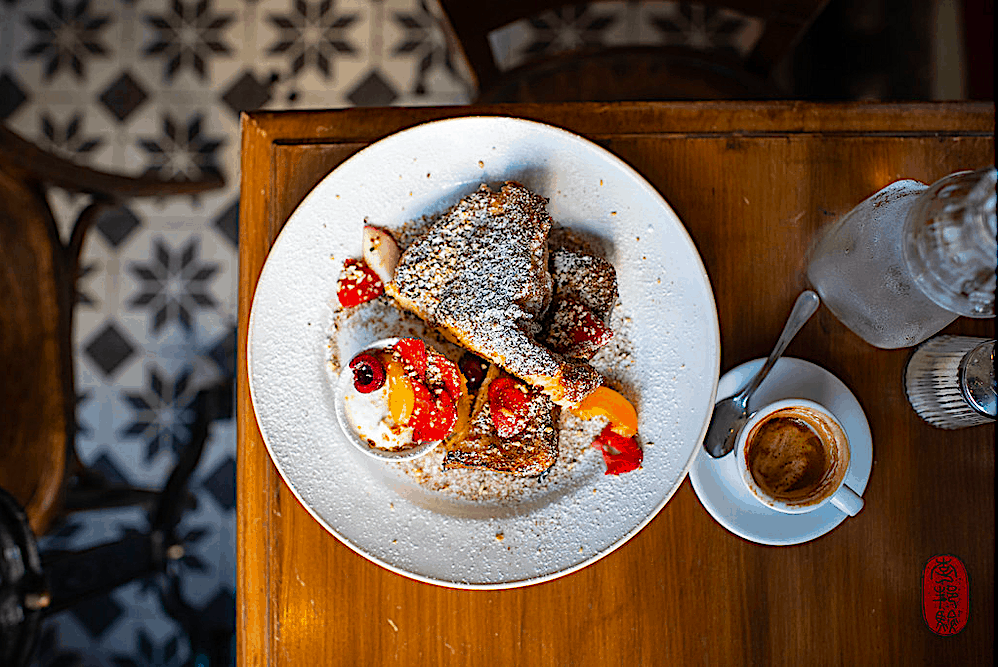 Aerial view of a plate of French toast with fruit and espresso at La Fontaine de Belleville in Paris.