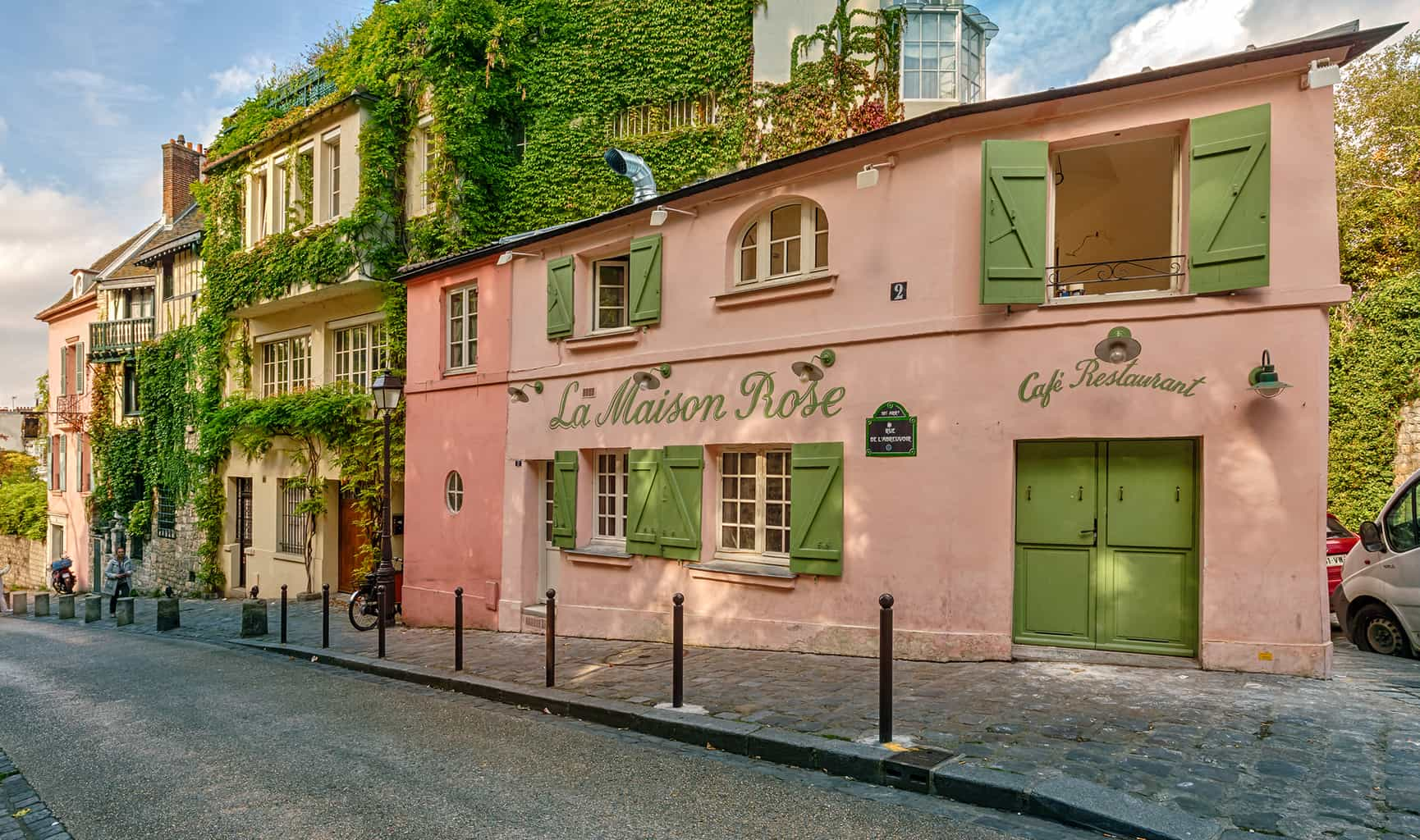 The beautiful, pale pink and lime green exterior of La Maison Rose in Montmartre, Paris.