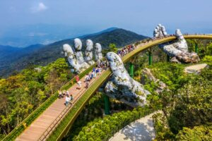 An aerial view of the Golden Bridge being lifted by two giant hands in the Ba Na Hills near Da Nang,