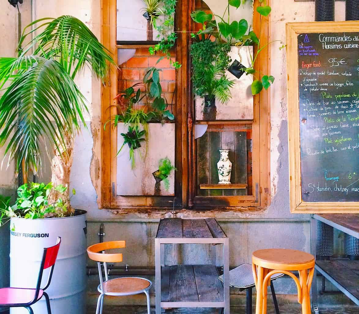 The quirky, plant-filled interior of La Recyclerie Cafe, one of the many hidden gems in Paris.