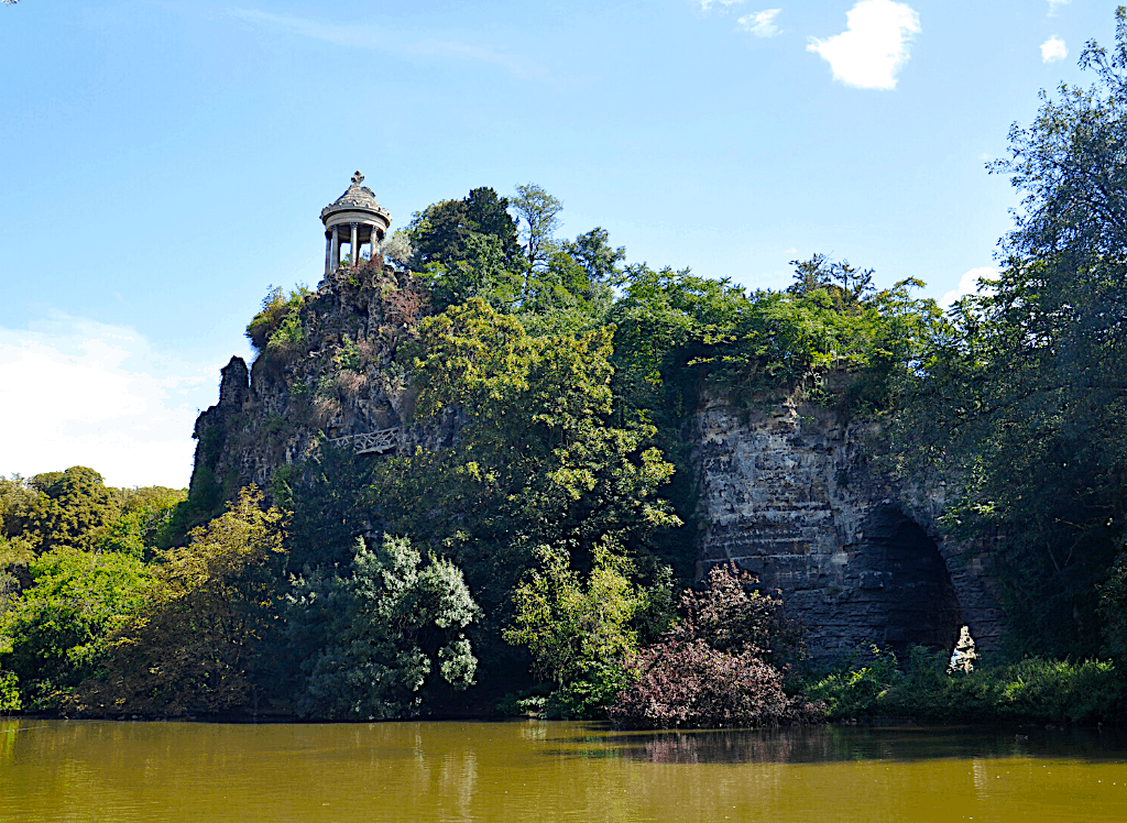 The scenic central lake and rock of Parc Des Buttes-Chaumont, one of the many hidden gems in Paris.