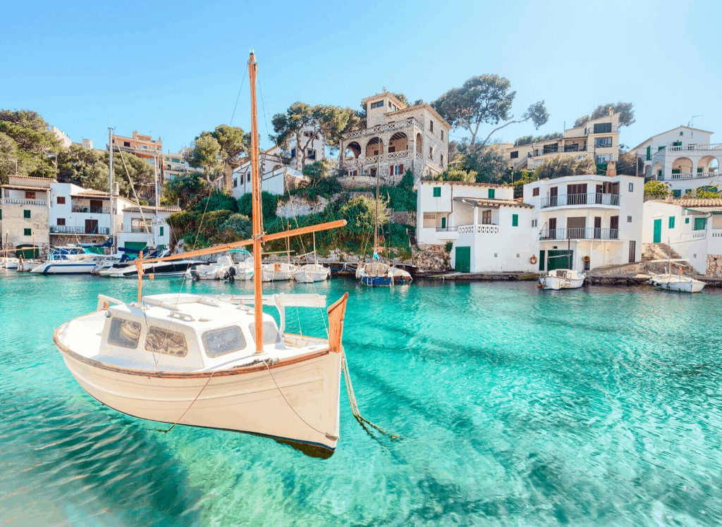 A sailboat docked in the turquoise waters along the coast of a Spanish village.