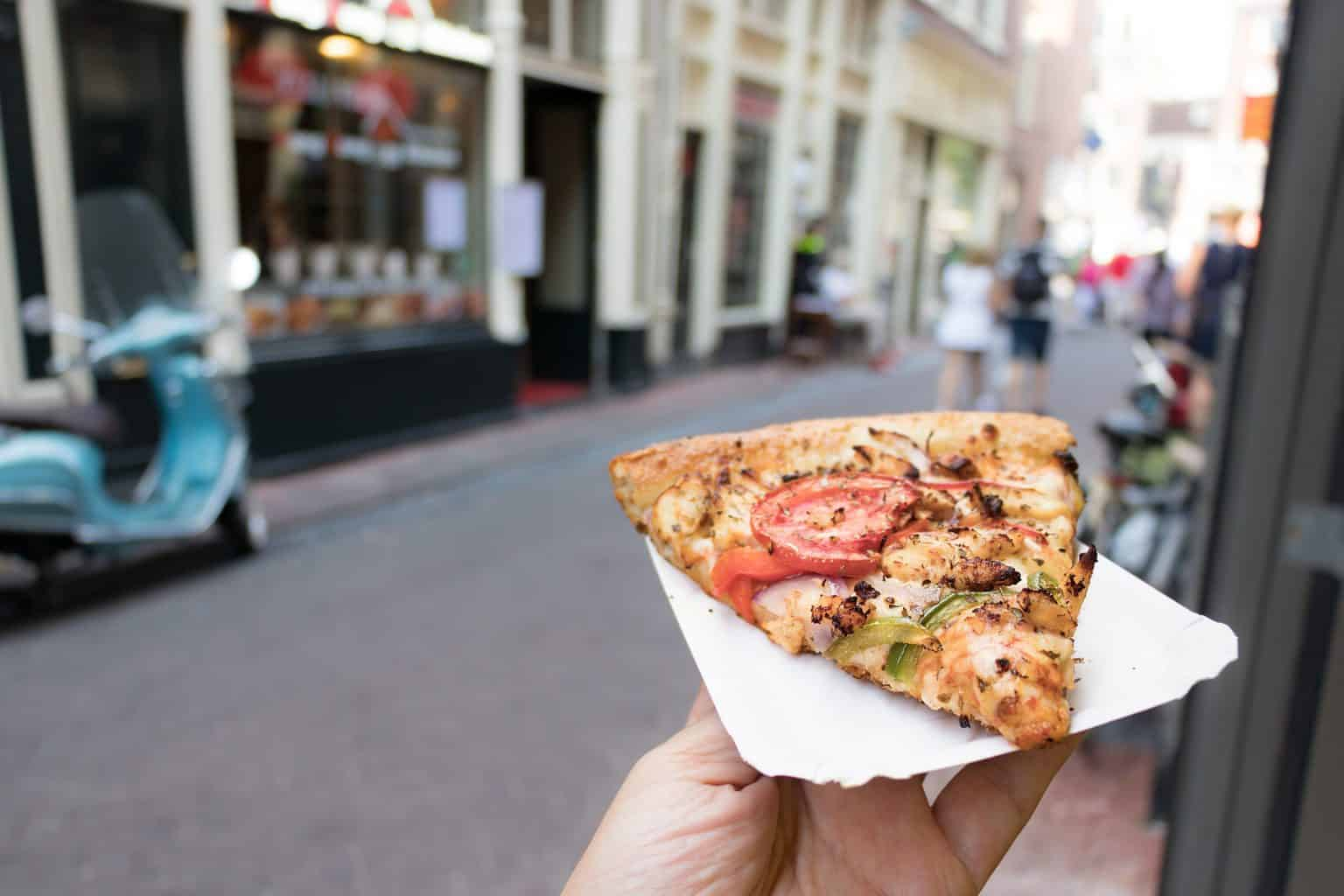 Enjoy a slice of pizza at Amsterdam's San Marco Pizzeria, home to the only boat-through in the world.
