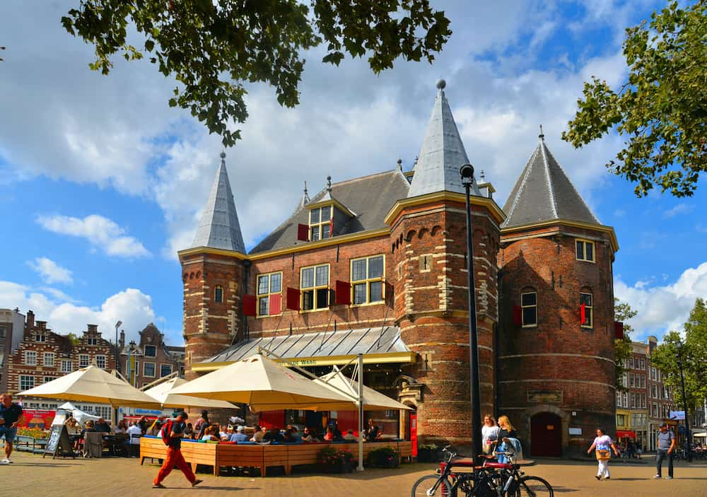 Cityscape with De Waag medieval building on Nieuwmarkt square or New Market square with people and blue cloudy sky,