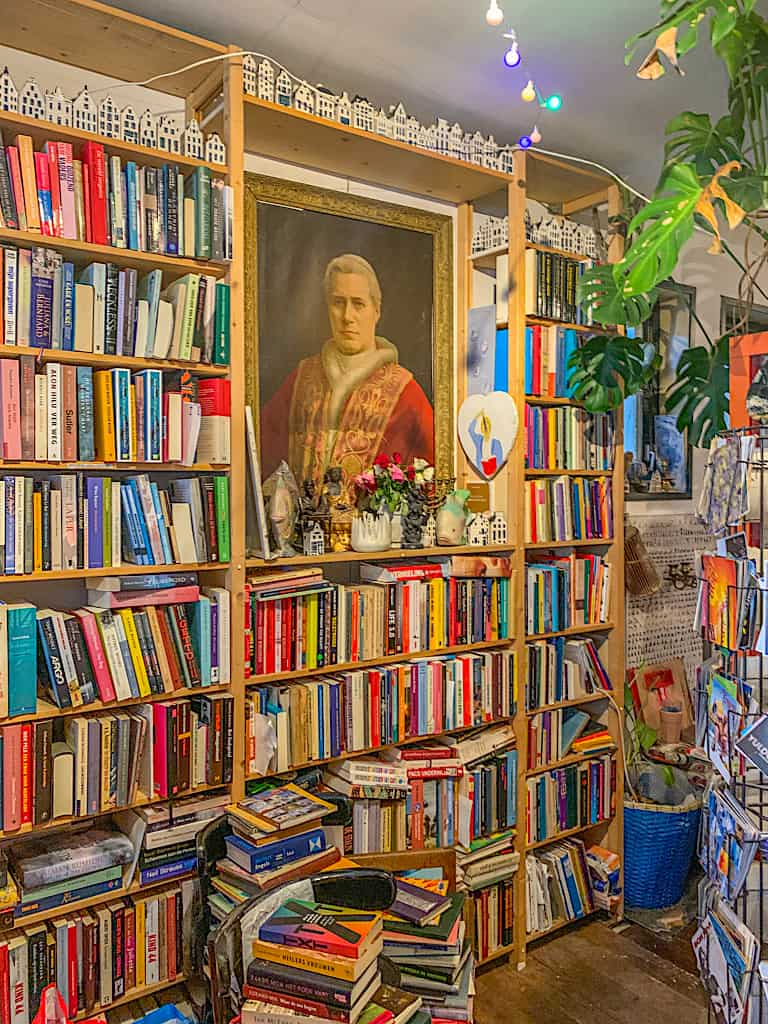 The bright, vibrant, and book-filled interior of the Happy Bookleman in Amsterdam.
