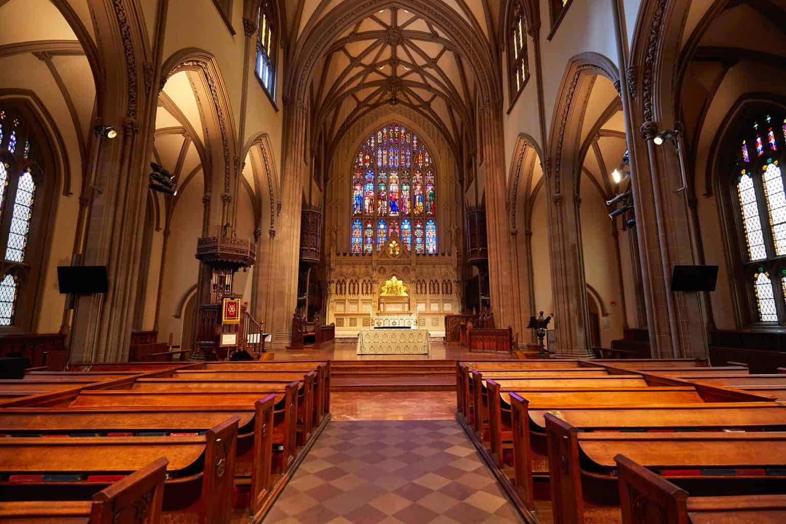 Beautiful stained glass windows and quaint wooden pews make up the interior of New York City's famous, Trinity Church,