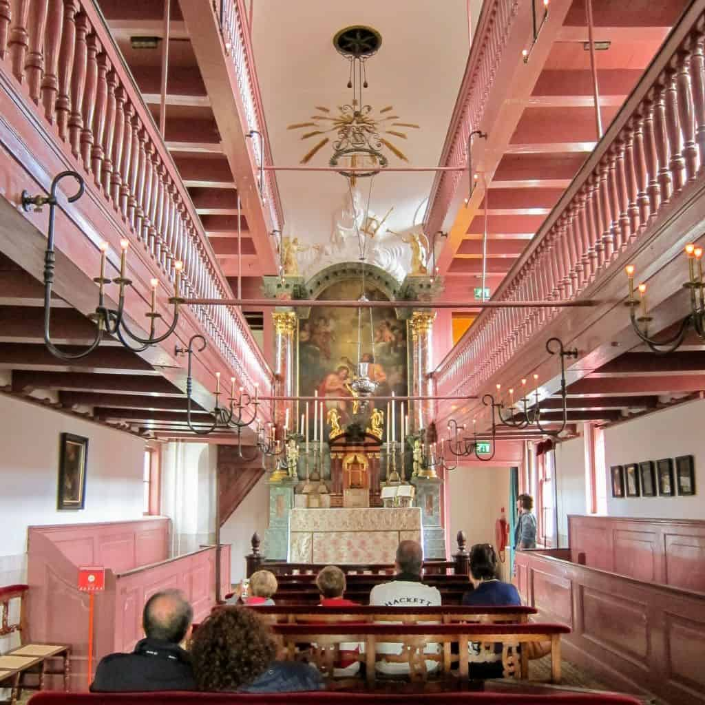 The main altar and vibrant, pink beauty of Ons' Lieve Heer op Solder, orthe Church of Our Lord in the Attic in Amsterdam.