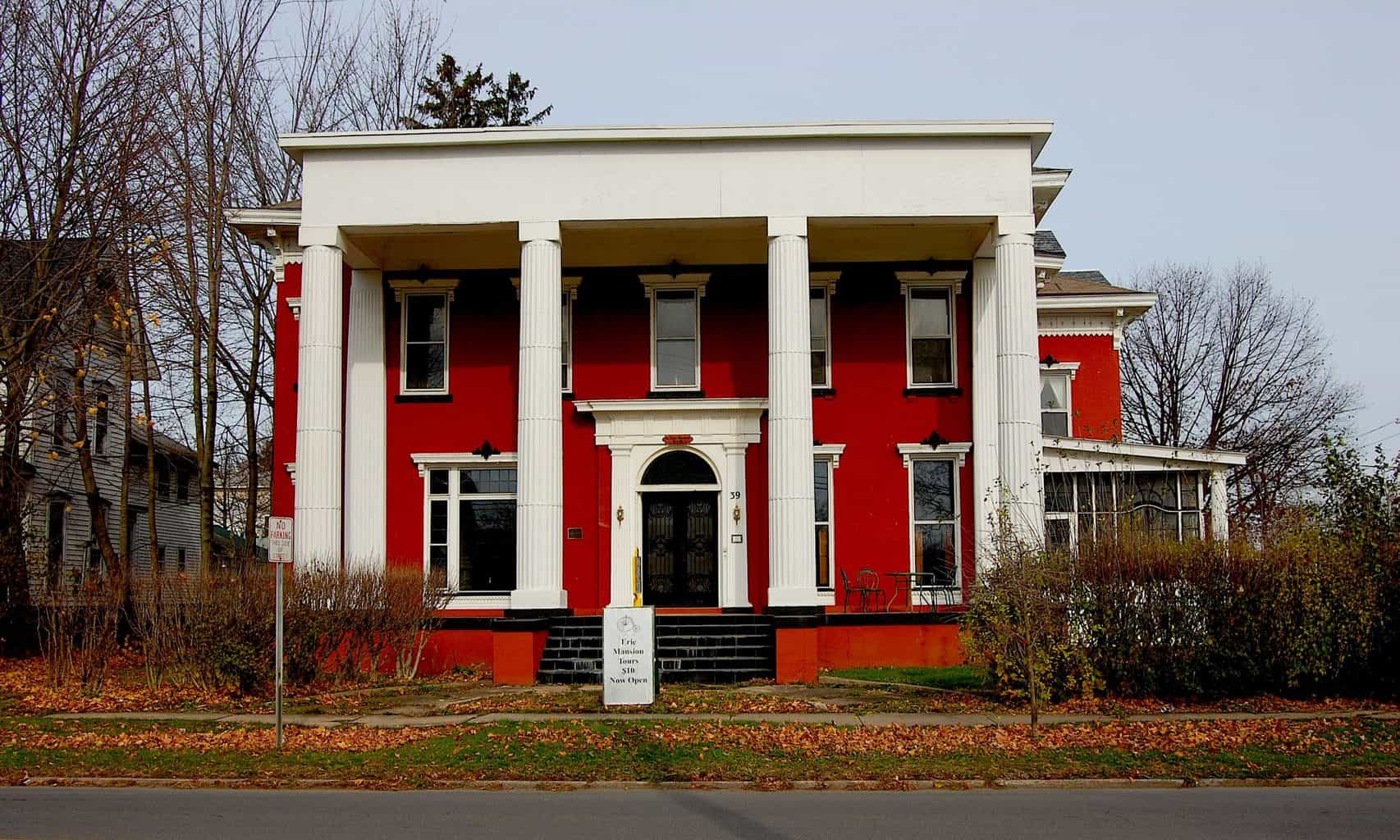 The beautiful, red exterior of the Erie Mansion Bed and Breakfast with giant white columns. One of the most haunted hotels in New York.