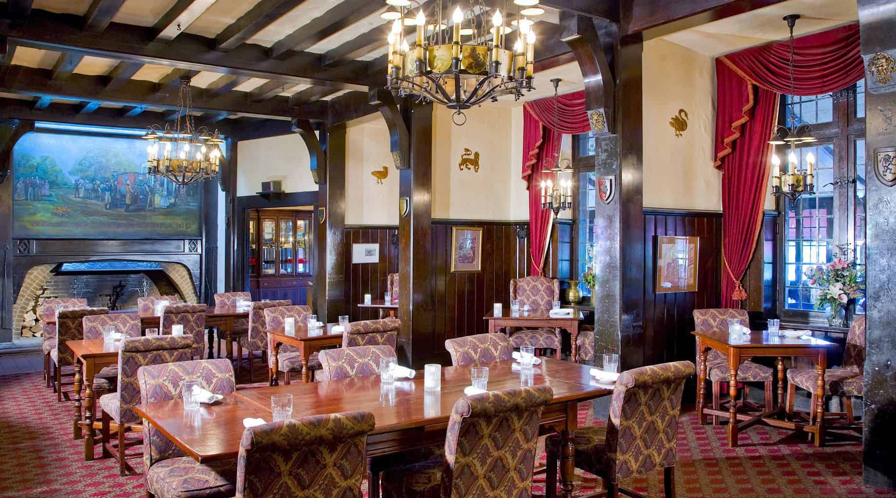 The refined and stately beamed ceilings, vibrant red curtains, upholstered chairs, and wood tables of the restuarant at the Red Coach Inn.