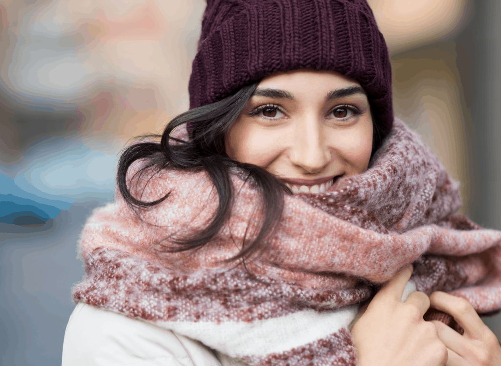 Woman wearing a warm scarf and hat - all of which are essential when packing for colder climates.