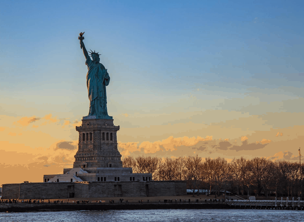 During your cruise, enjoy a beautiful view of the statue of liberty at sunset.