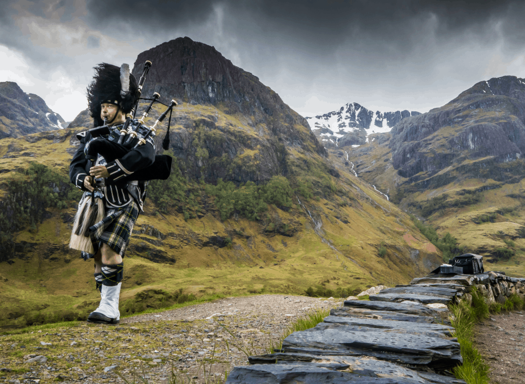 A Scottish man wearing a kilt and playing the bagpipes in the Scottish Highlands.