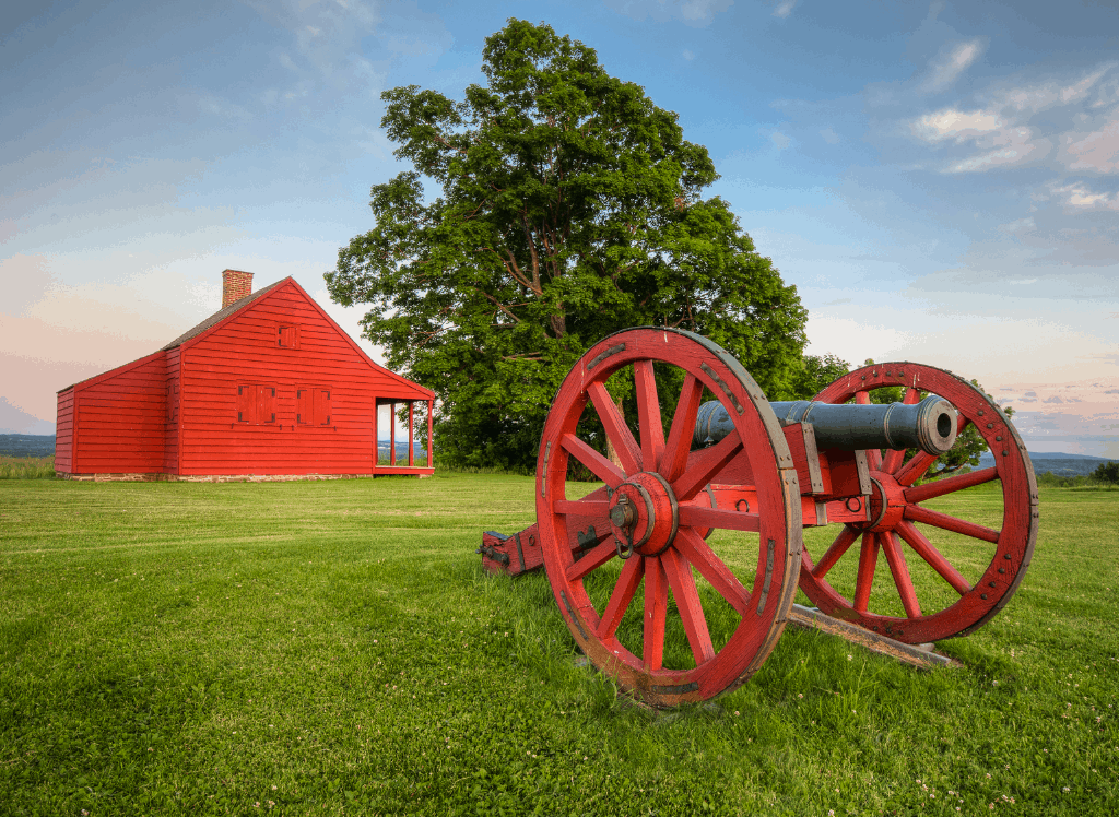 A canon in front of the red Neilson Farmhouse in Saratoga National Historical Park.