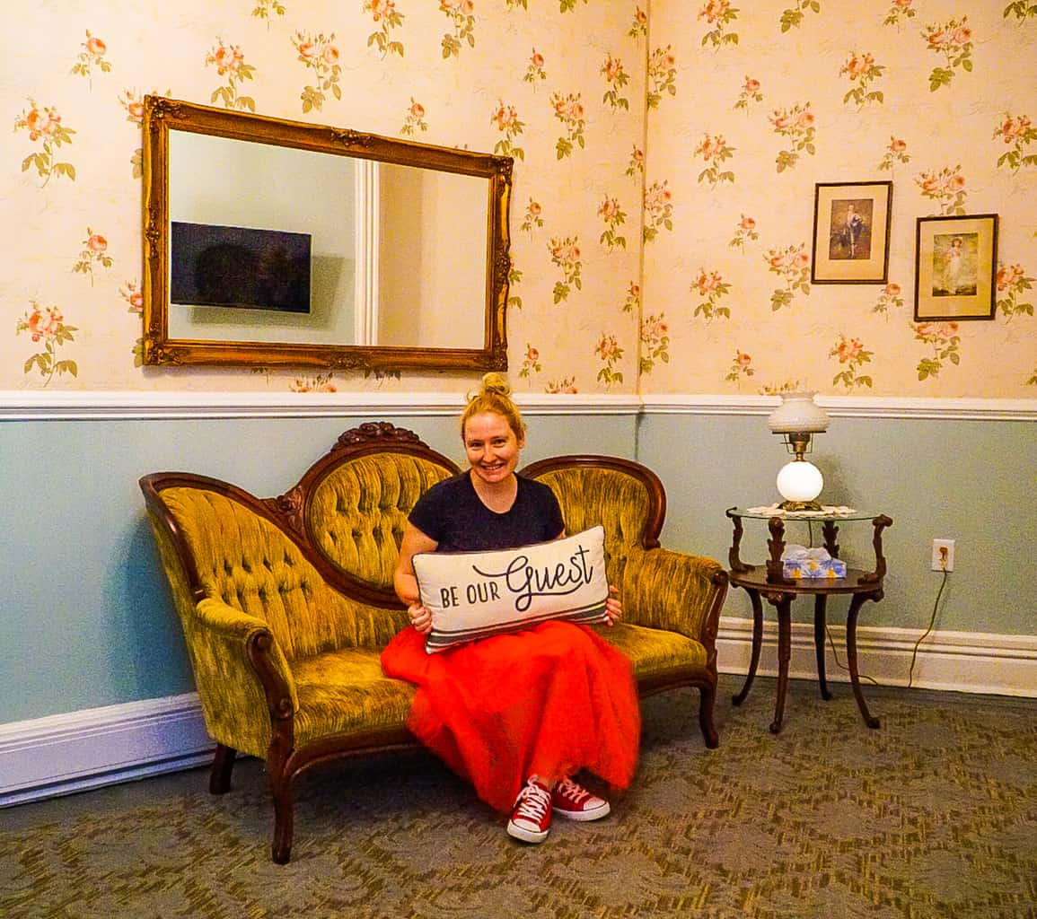 Holding a pillow while sitting on a yellow sofa inside the parlor of the Historic Hotel Broadalbin's bridal suite.