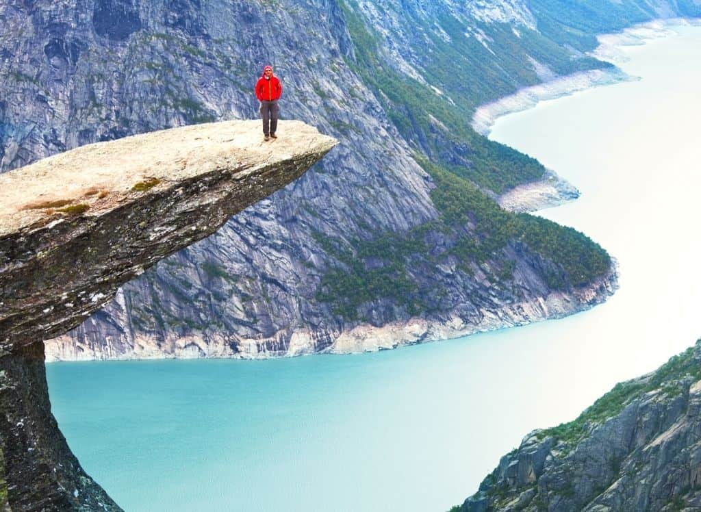 A hiker in a red jacket standing on top of a rock at Trolltunga.
