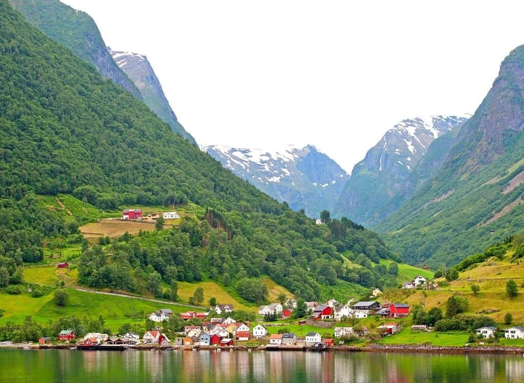 Houses siting along the water at the base of a fjord in Flam, Norway.