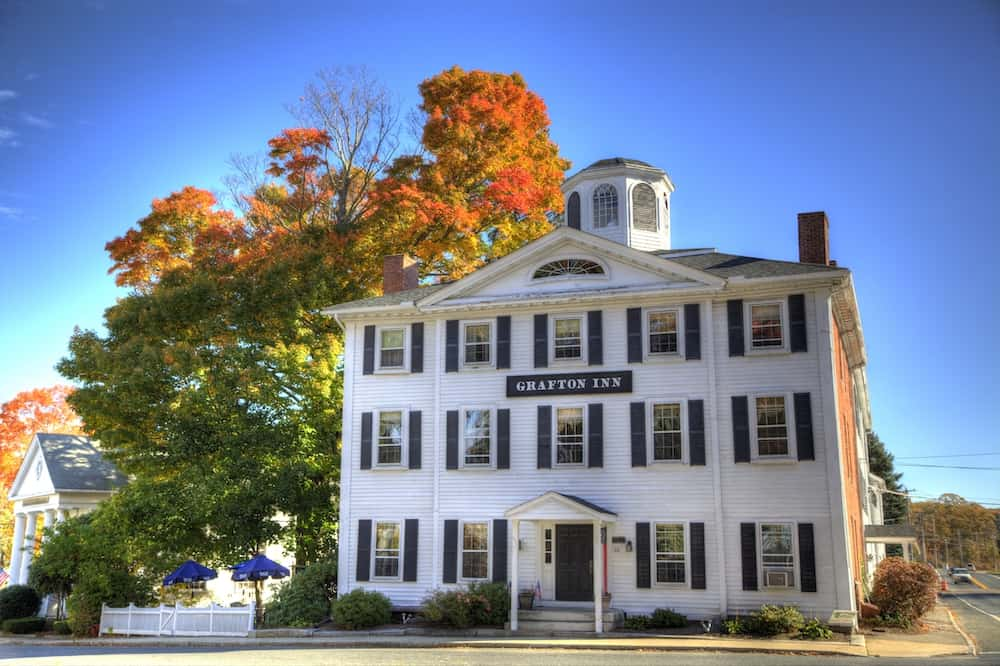 The white facade of the Grafton Inn with vibrant fall foliage in the background.