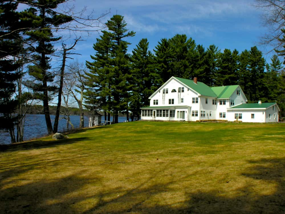 The white exterior and green roof of the Wolf Cove Inn in Poland, Maine