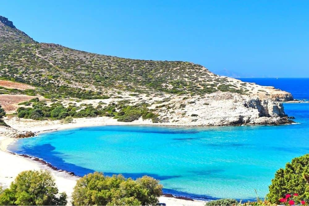 The turquoise blue waters and sandy beach of Antiparos in Greece.