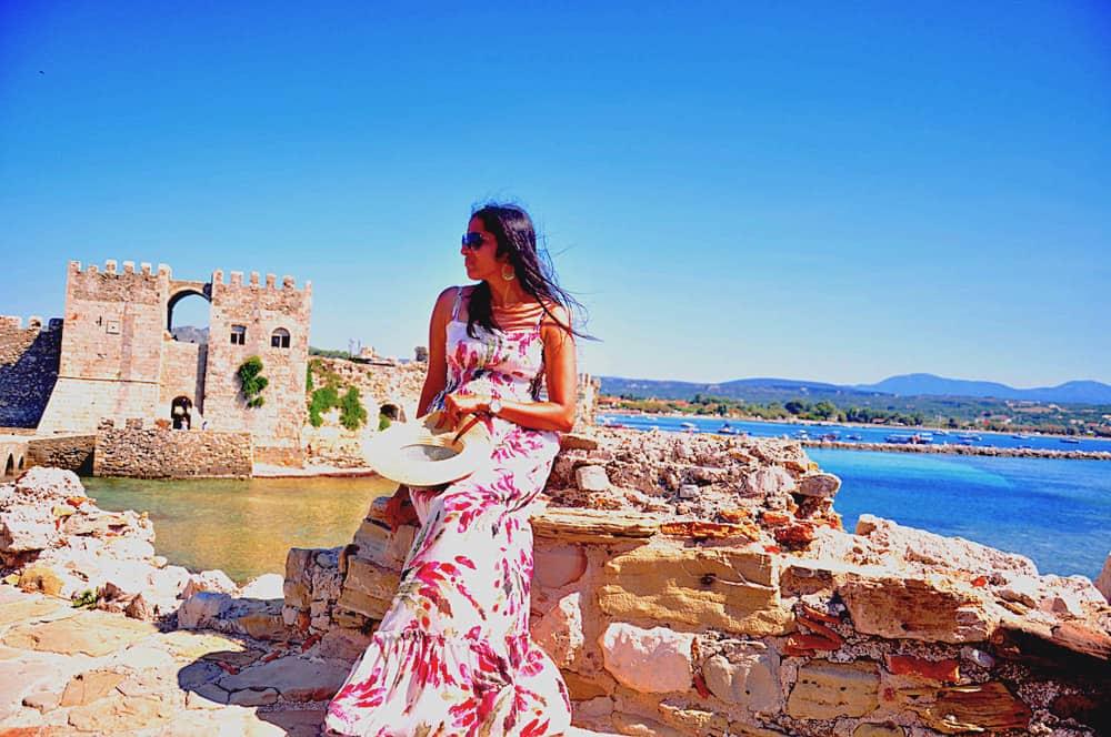 A girl sitting near the strange of Methoni Castle in Greece.