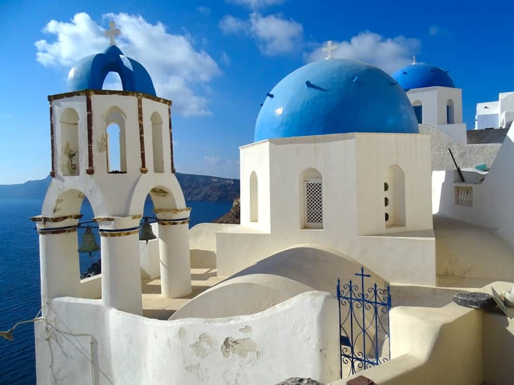 Traditional white washed buildings with blue-domed roofs in Santorini.