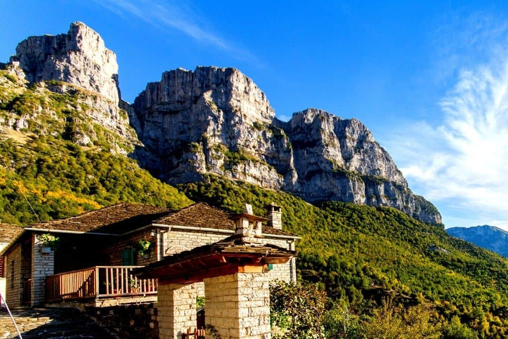 Homes sitting at the foot of the vibrant green hills in Vikos Aoos National Park.