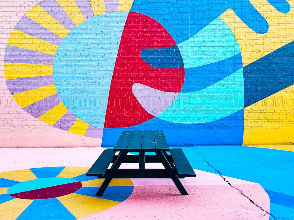 Picnic Table and Wall Art outside of Fog Bar