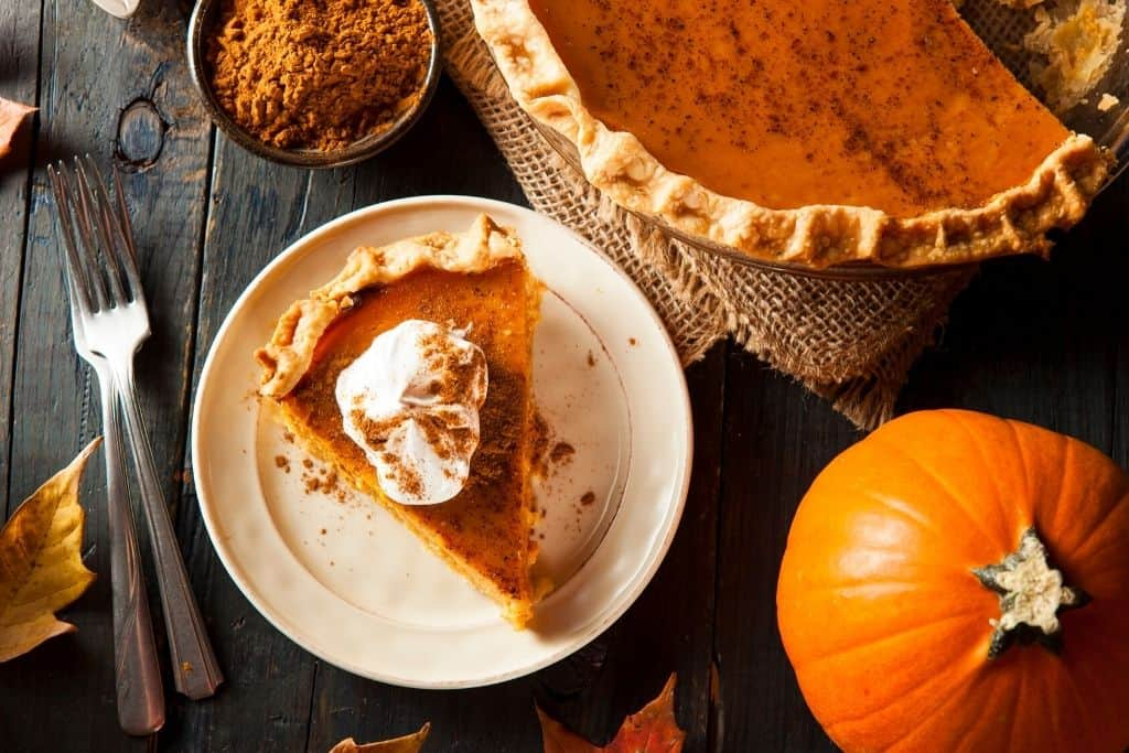 A slice of pumpkin pie with whipped cream on top.