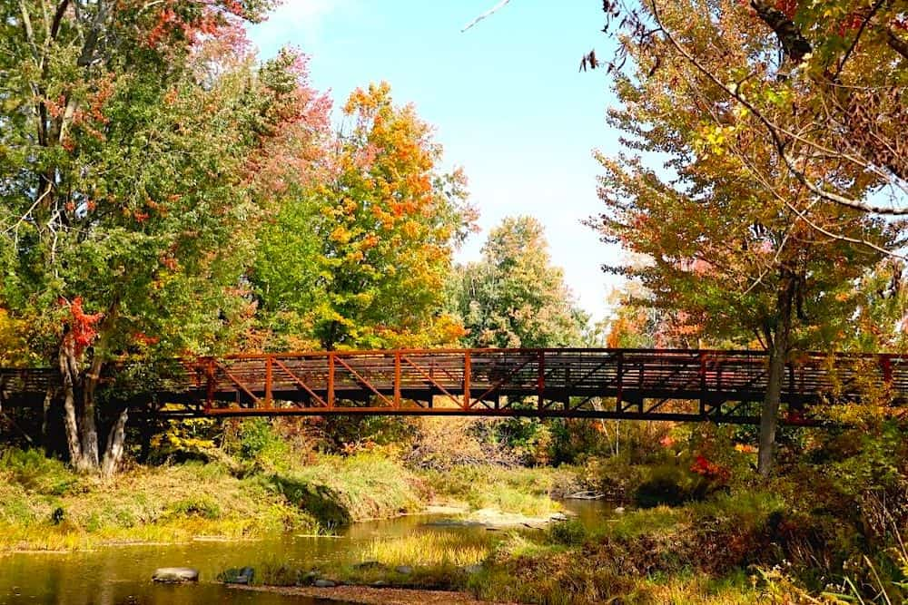 Maine in the fall with a wooden bridge over a stream surrounded by foliage.