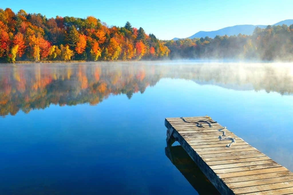 A lake in Vermont with a dock and fall foliage all around it.