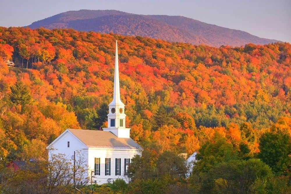 A white church surrounded by fall foliage in rural Vermont.