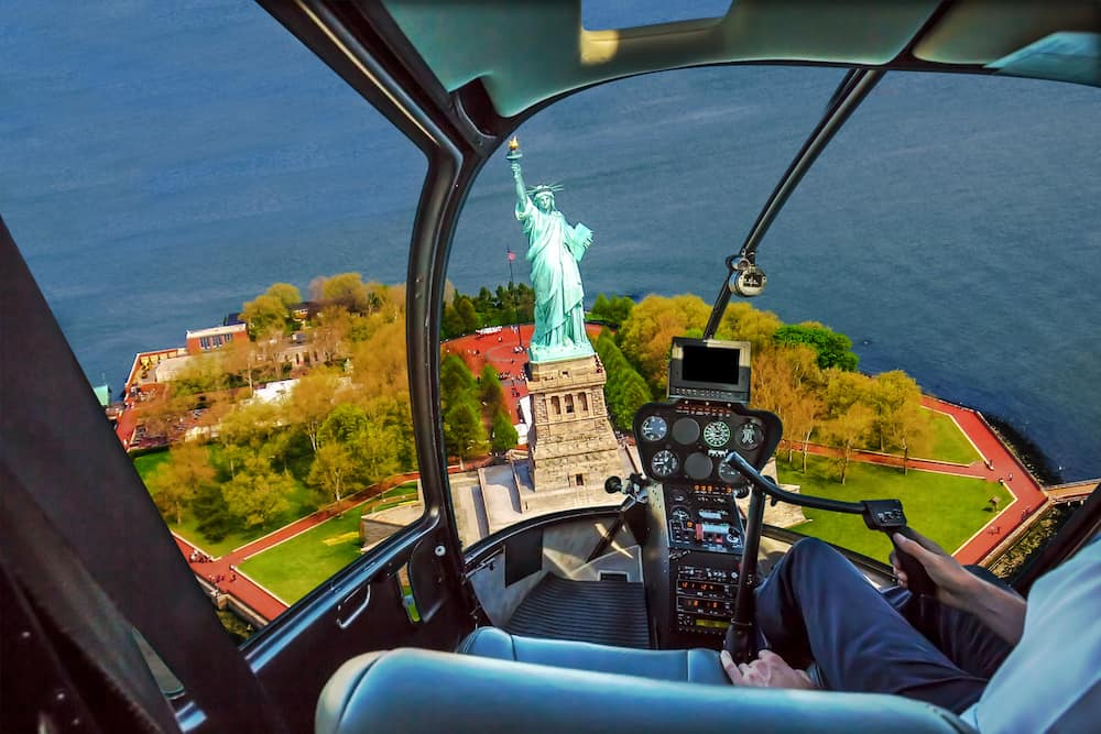 A helicopter pilot looking out at the Statue of Liberty. A helicopter tour is one of the many things to do in NYC on your birthday.
