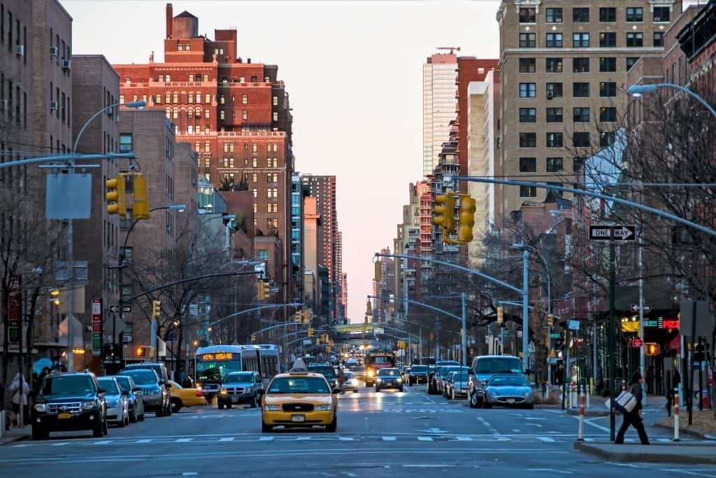 View down a busy NYC street with a yellow cab where people speak NYC slang.