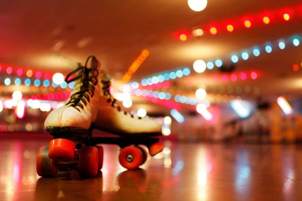 Two white roller-skate with pink stoppers and wheels at a roller disco.