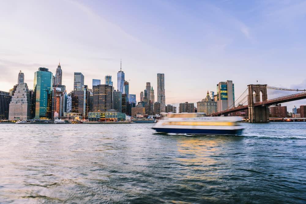 A boat cruising through New York Harbor at sunset.