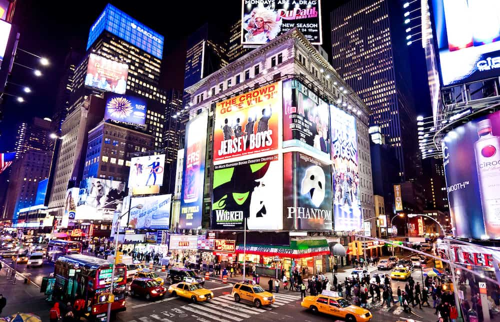 The bright lights and marquee signs for Broadway shoes in Times Square.