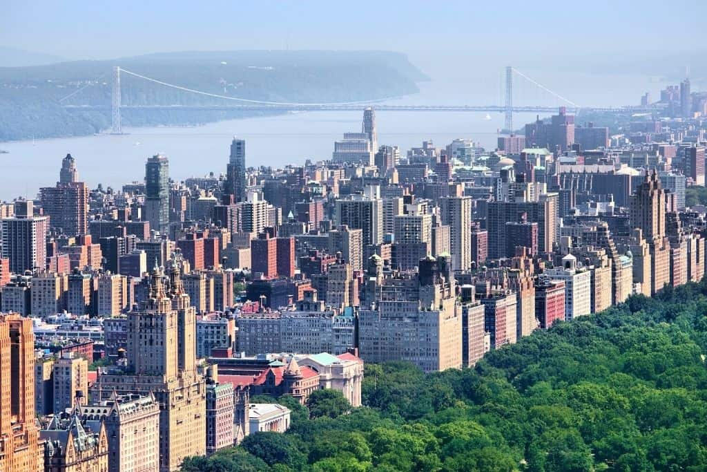 Aerial view of Central Park and the buildings on the Upper West Side, with the George Washington Bridge in the background.