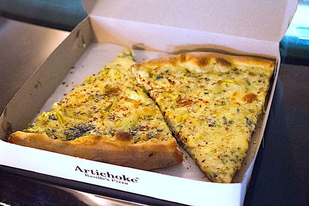 Two slices of artichoke spinach pizza in a pizza box from Artichoke Basille pizza.