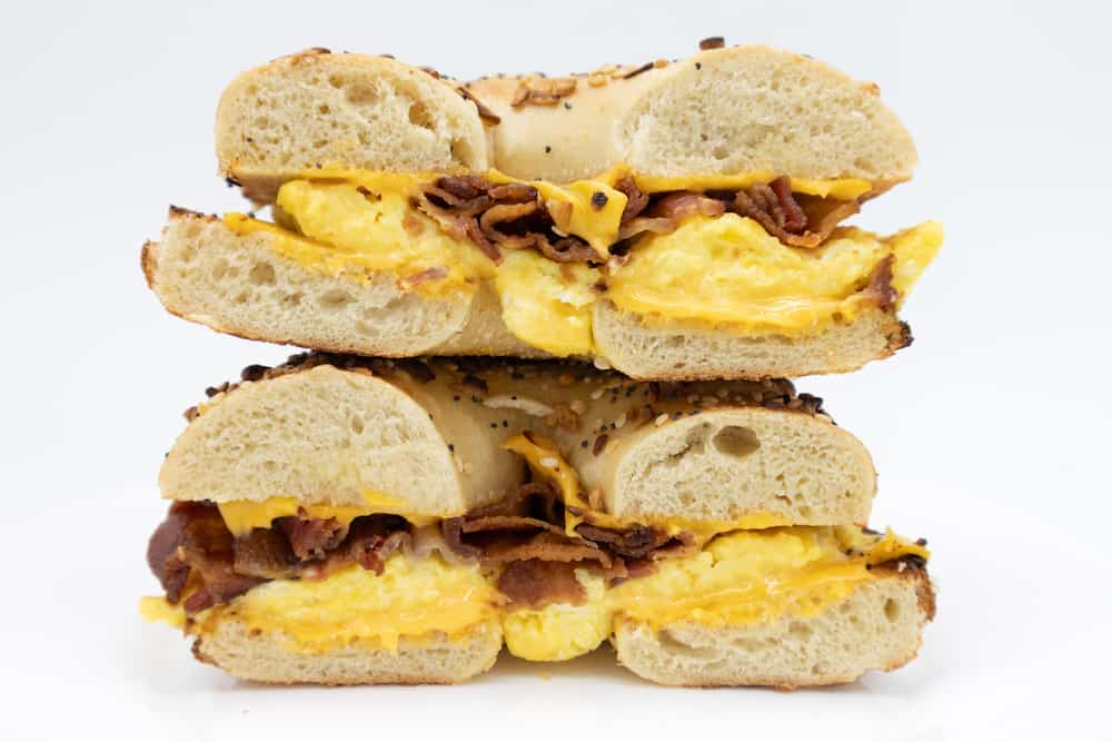 A cut in half side view of an everything bagel with bacon eggs and cheese on a white plate with a white background.