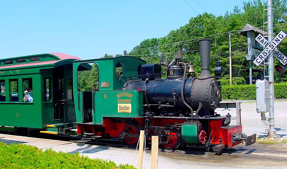 Vintage green train coming down the track at Boothbay Railway Village.