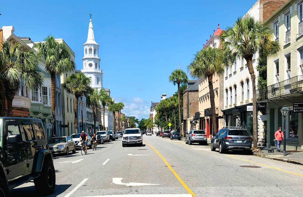 People riding their bikes and cars driving through the center of Charleston, South Carolina.