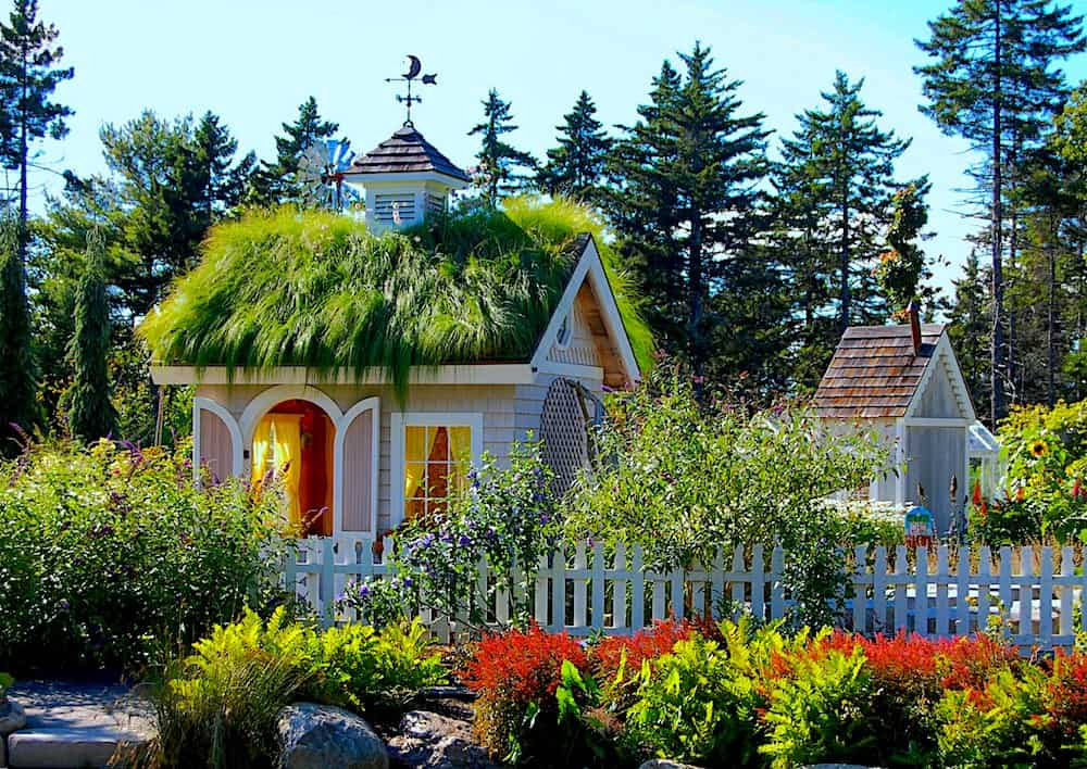 Quaint New England home covered in greenery on the roof and surrounded by flowers at the Coastal Maine Botanical Gardens