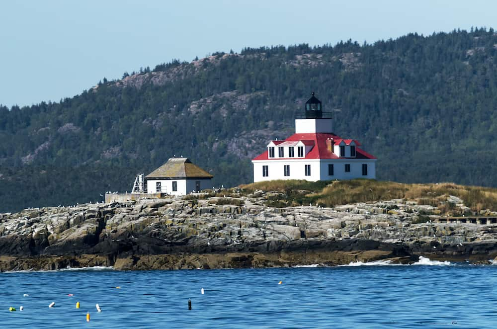 Egg Rock lighthouse in Maine with seagulls standing on the rocks and Acadia National Parks Cadillac Mountain behind it on a summer afternoon. (Egg Rock lighthouse in Maine with seagulls standing on the rocks and Acadia National Parks Cadillac Mountain
