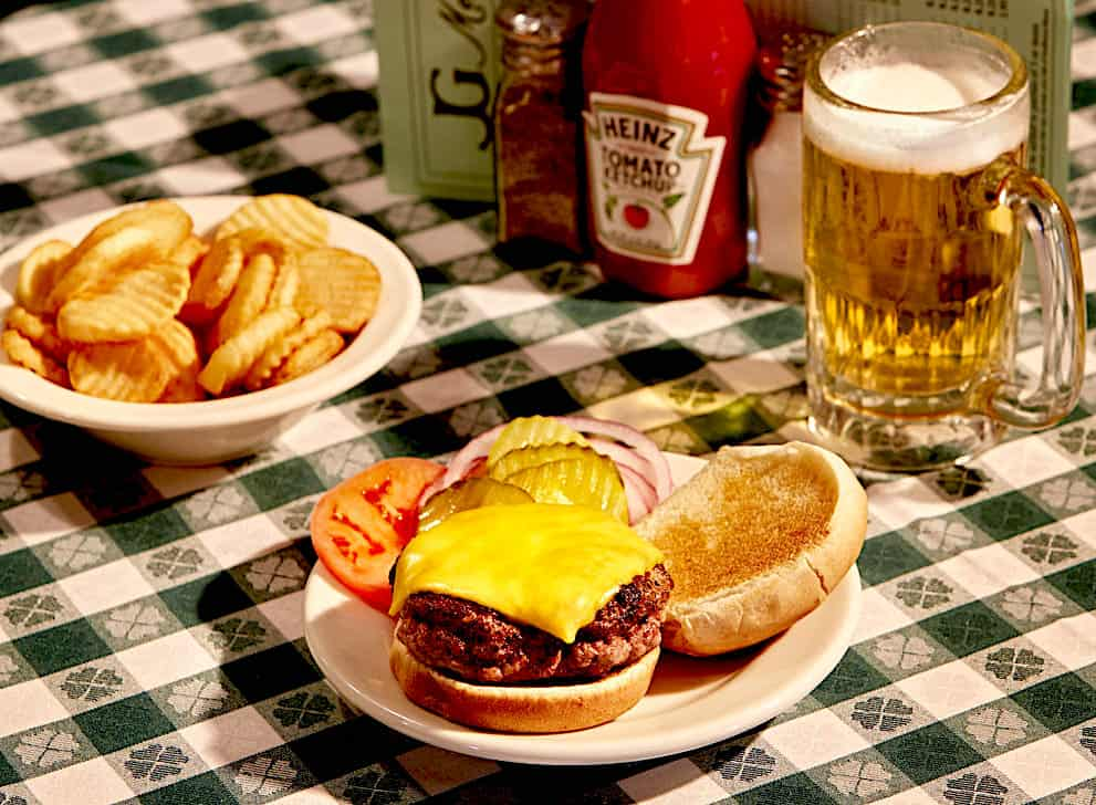 A cheeseburger on a green and white table cloth with a beer and fries at J.G. Melon's one of the places you must eat in NYC.