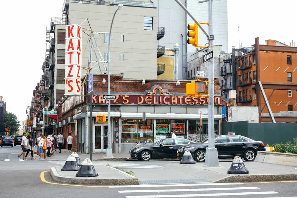 The exterior of Katz's deli on the Lower East Side of NYC with people walking out front.