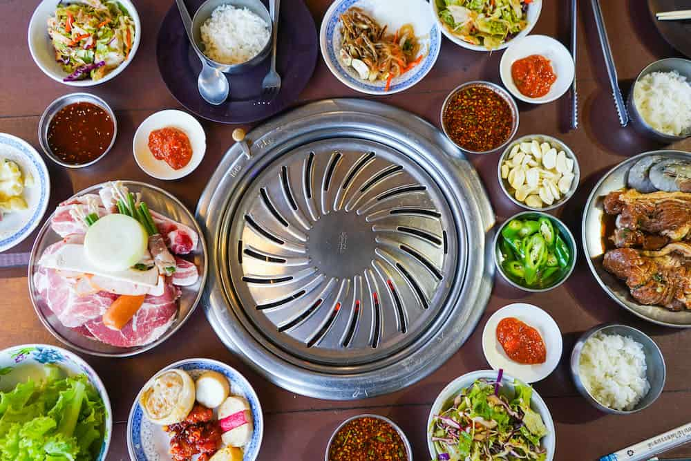 Authentic Korean bbq with pork and various side dishes around an in-table grill.